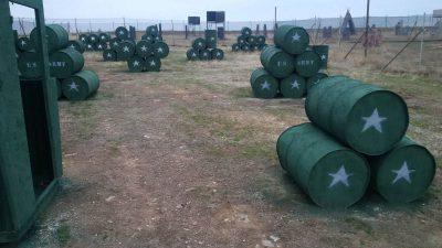 Escenario de paintball con barriles pintados de verde para tu despedida de soltero