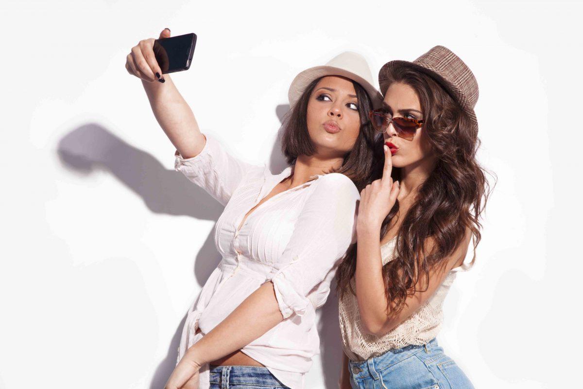 Dos chicas jóvenes echándose una foto con un teléfono movil.